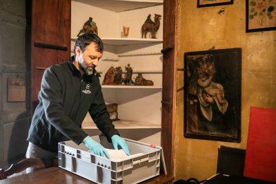 El tècnic dels Museus d'Olot Xevi Roura recollint les peces de Ramon Amadeu a Can Bolós. Foto: Martí Albesa.